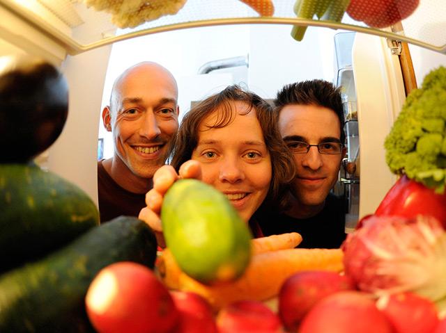 Zwei Männer und eine Frau blicken in einen mit Gemüse gefüllten Kühlschrank