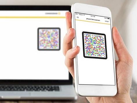 Ein Handy zeigt ein Quadrat aus bunten Pixeln, den Photo-TAN, an