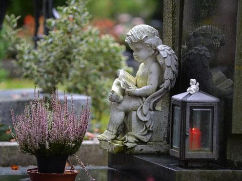 Grabstein mit Blumenstock, brennender Kerze und Engel aus Stein