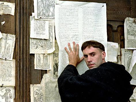 """Joseph Fiennes als Luther im bekannten Film """"Luther"""" (2003). Er hämmert die Thesen an die Schlosskirche Wittenberg"""