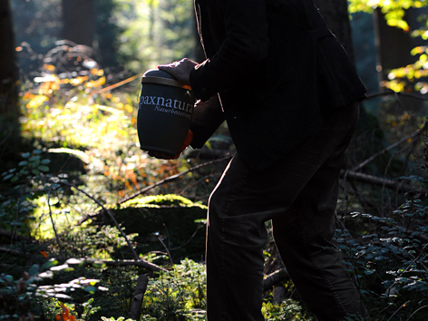 Ein Mann in einem Wald hält eine Urne in der Hand