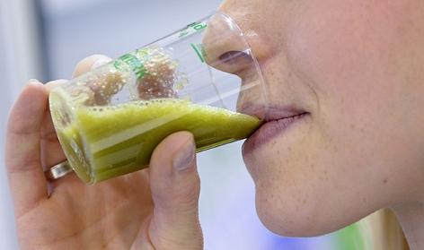 Eine Frau trinkt ein Smoothie mit Feldsalat