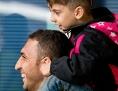 Ein Flüchtlingsvater mit Kind auf den Schultern freut sich über ein Spielzeug, das ihm jemand entgegenstreckt