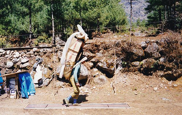 Nepalesischer Träger, schwer bepackt mit aufgetürmten Kisten in einem Korb