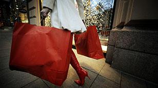 Frau trägt rote Taschen mit Geschenken