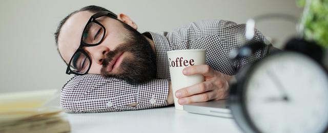 Ein erschöpfter Mann schläft mit einer Tasse Kaffe auf seiner Arbeitstischplatte