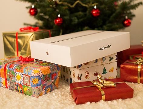 Weihnachtsgeschenke liegen unter einem Christbaum, deutlich sichtbar ist die Verpackung eines Apple Macbook Pro