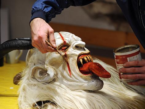Larvenschnitzer beim Bemalen einer Krampusmaske (Salzburg)