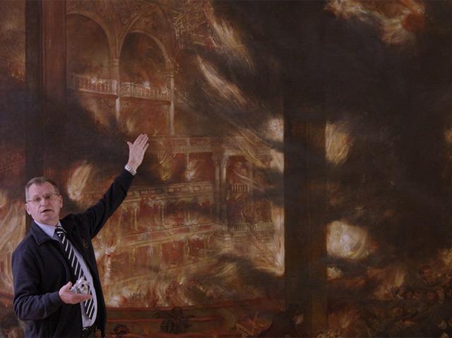 Heinrich Krenn, der Leiter des Feuerwehrarchivs, vor einem Gemälde, das den Brand des Ringtheaters zeigt