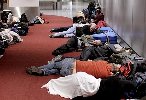 Urlauber schlafen auf dem Boden in der Abflughalle des Flughafens Düsseldorf