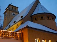 angeschneite Grazer Kreuzkirche von außen in der Dämmerung
