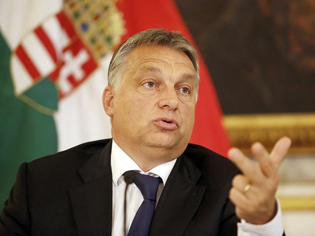Ungarns Präsident Viktor Orban gestikuliert vor einer ungarischen Fahne