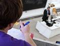 Ein Student im Hörsaal einer Uni blickt auf den Vortragenden