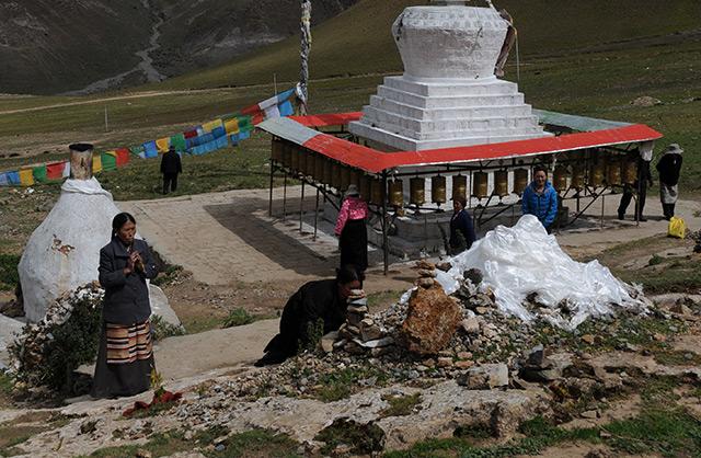 Hand- und Fußabdrücke von Chusang, im Hintergrund ein buddhistischer Kultbau