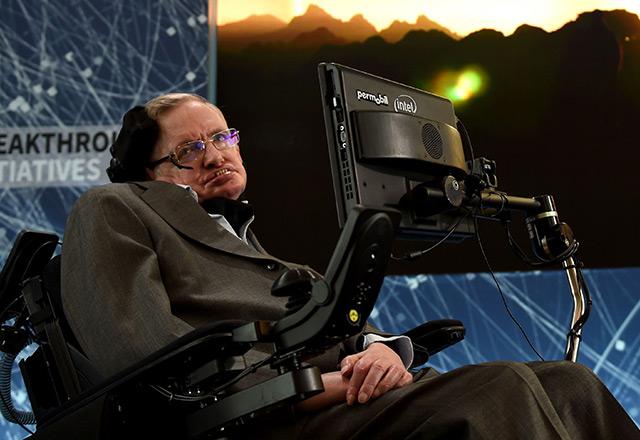 Stephen Hawking im April 2016 in New York vor einem Hintergrund mit Motiven aus dem Weltall