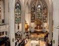 gothischer Kirchenraum mit farbenreichen hohen Fenstern während eines Gottesdienstes
