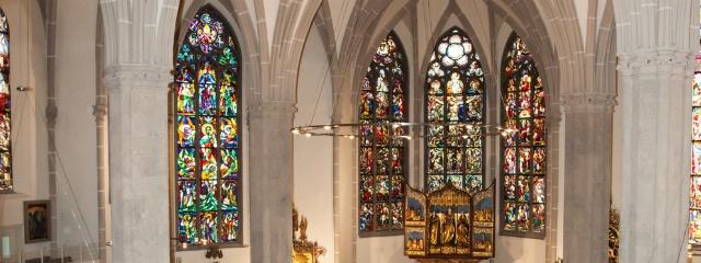gothischer Kirchenraum mit farbenreichen hohen Fenstern