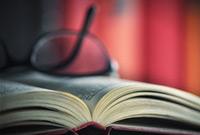 Auf einem aufgeschlagenen Buch liegt eine Brille, Bücher