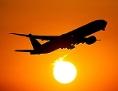 Eine Boeing 777 startet bei Sonnenuntergang vom Flughafen
