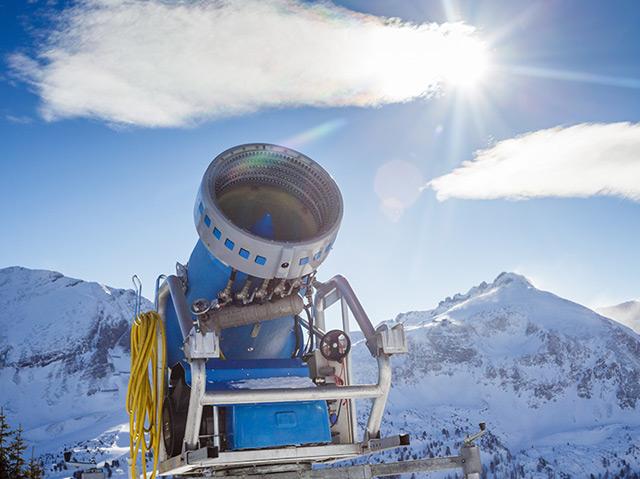 Schneekanone vor blauem Himmel, die Kunstschnee produziert