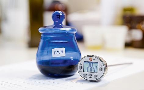 eine Olivenölprobe in einer blauen Flasche