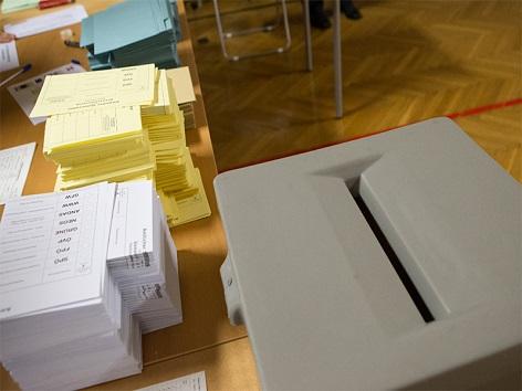 Eine Wahlurne mit Wahlzetteln