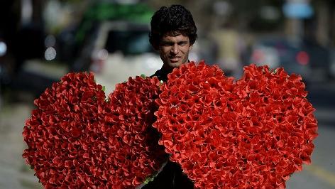 Ein pakistanischer Händler in Islamabad mit zwei herzförmigen Blumenbuquets in den Händen