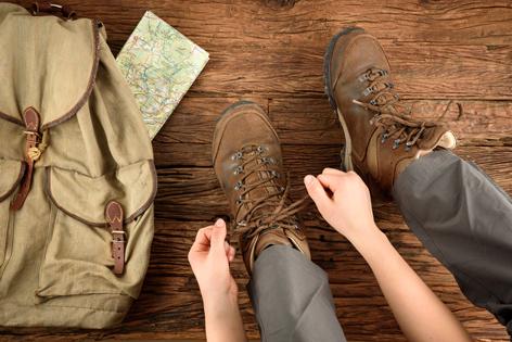 Wanderin schnürt sich die Wanderschuhe zu