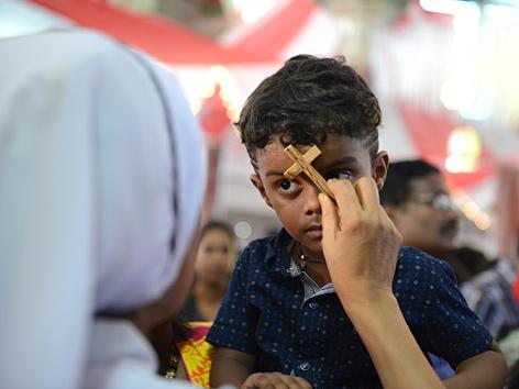Eine katholische Nonne in Hyderabad, Indien, hält einem Buben ein Holzkreuz an die Stirn