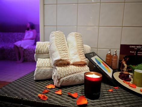 Kerze, Duftflaschen, Handtücher liegen auf einem Tisch vor dem Dampfbad