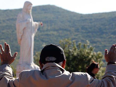 Ein Mann mit erhobenen Armen vor der Marienstatue im Pilgerort Medjugorje