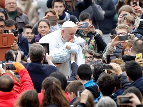 Papst Franziskus küsst ein Baby in einer Menschenmenge