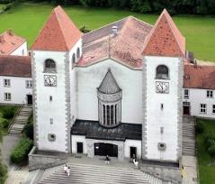 mächtiges Gotteshaus mit zwei Türmen und breiter Eingangstreppe außen bei Tag im Sommer, von oben gesehen