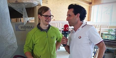 Ö3-Mikromann Tom Walek besucht Tischler Flo Oswald an seinem Arbeitsplatz und steckt ein Stück Zirbenholz ein