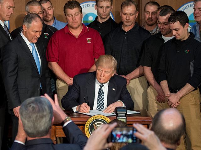 Donald Trump unterschreibt das Dekret - umbegeben von Bergarbeitern