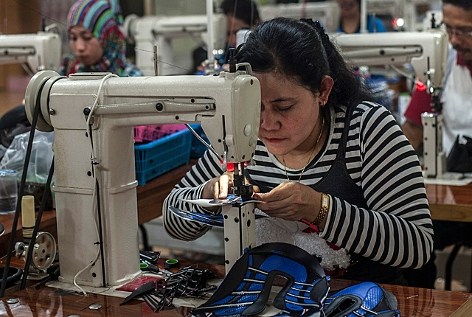 eine Frau näht Schuhe in einer Fabrik in Indonesien