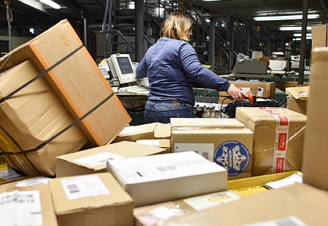 Eine Mitarbeiterin sortiert Pakete