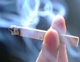 Ein Mann hält eine Zigarette in der Hand, die qualmt