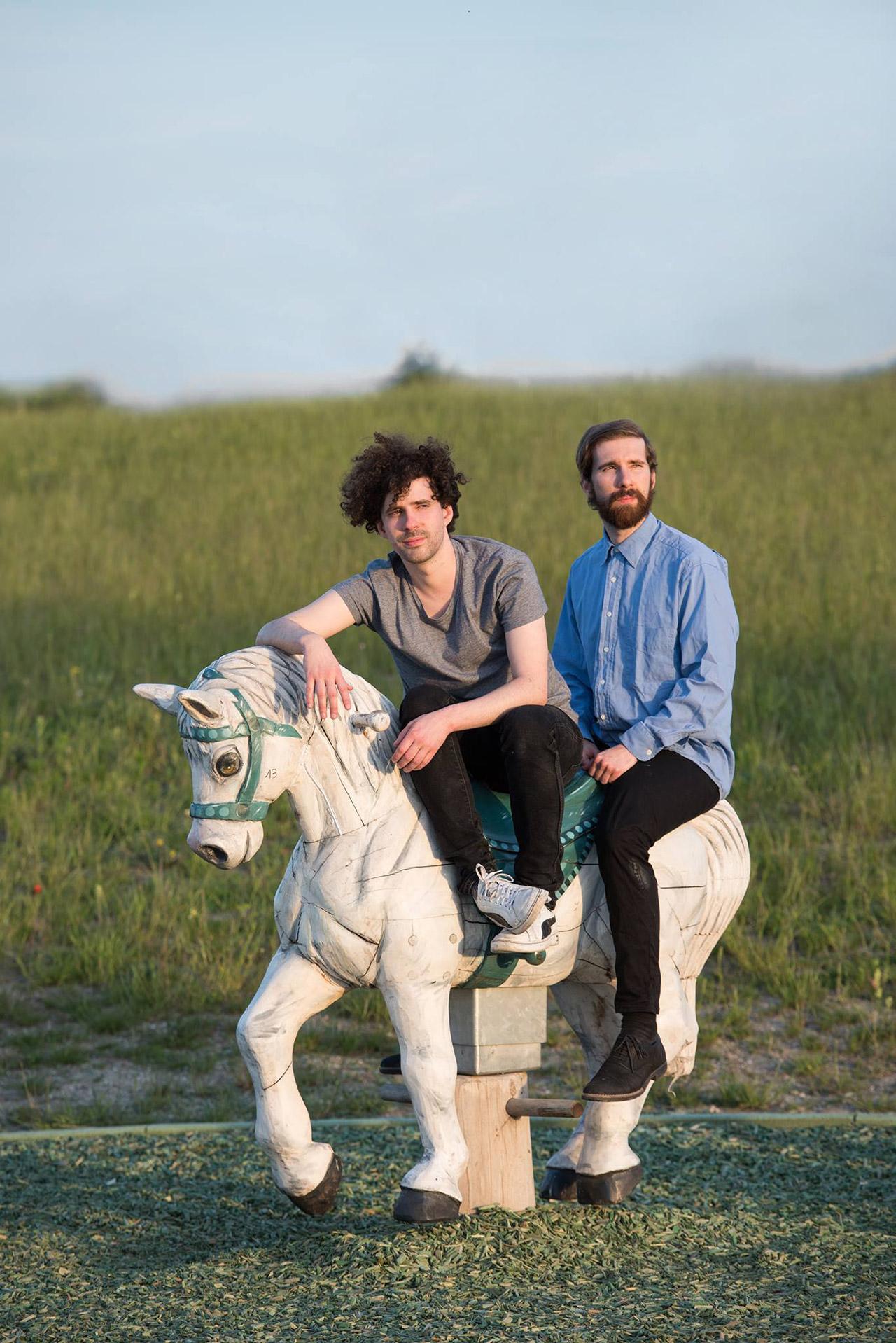 Zwei Männer auf einem Holzpferd