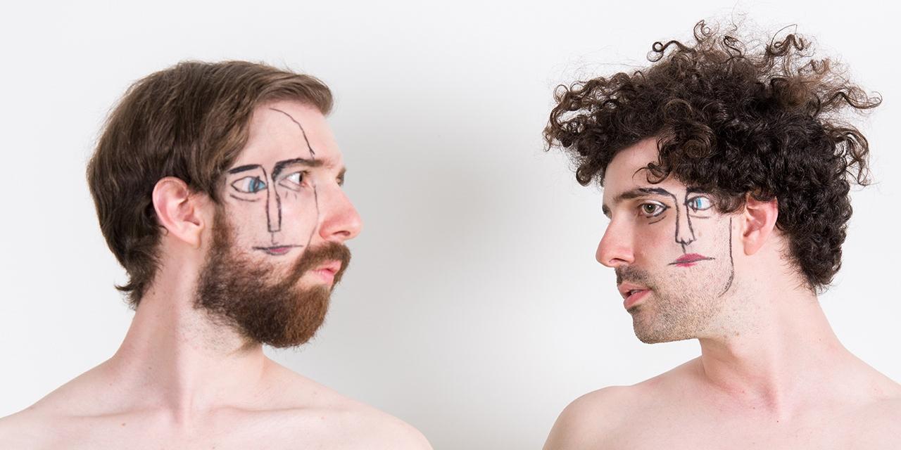 Zwei nackte Männer mit aufgemalten Gesichtern
