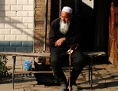 Ein uigurischer alter Mann sitzt vor seinem Haus in der chinesischen Provinz Xinjiang