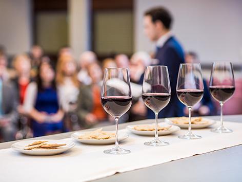 Abendmahl bei den Zeugen Jehovas: Gläser mit Rotwein und Brot auf Tellern