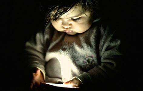 Ein zehn Monate altes Baby blickt auf ein Handy