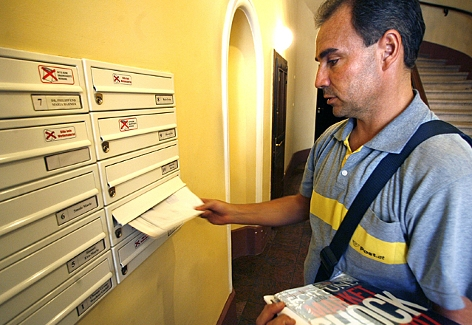 Ein Briefträger beim Verteilen der Post in die Briefkästen