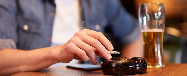 Ein Mann in einer Bar mit Zigarette und Bier