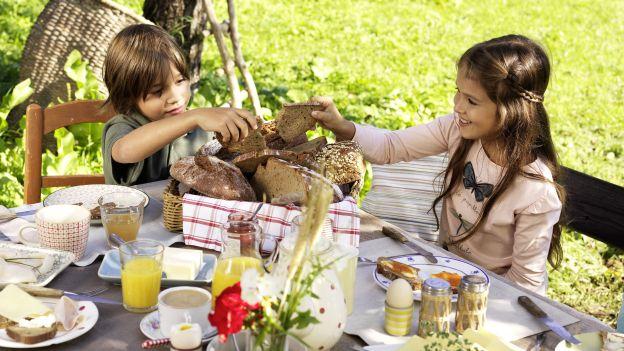 2 Kinder frühstücken im Grünen