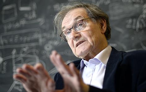 Der britische Mathematiker und Physiker Sir Roger Penrose 2015 vor einer Wand mit mathematischen Formeln
