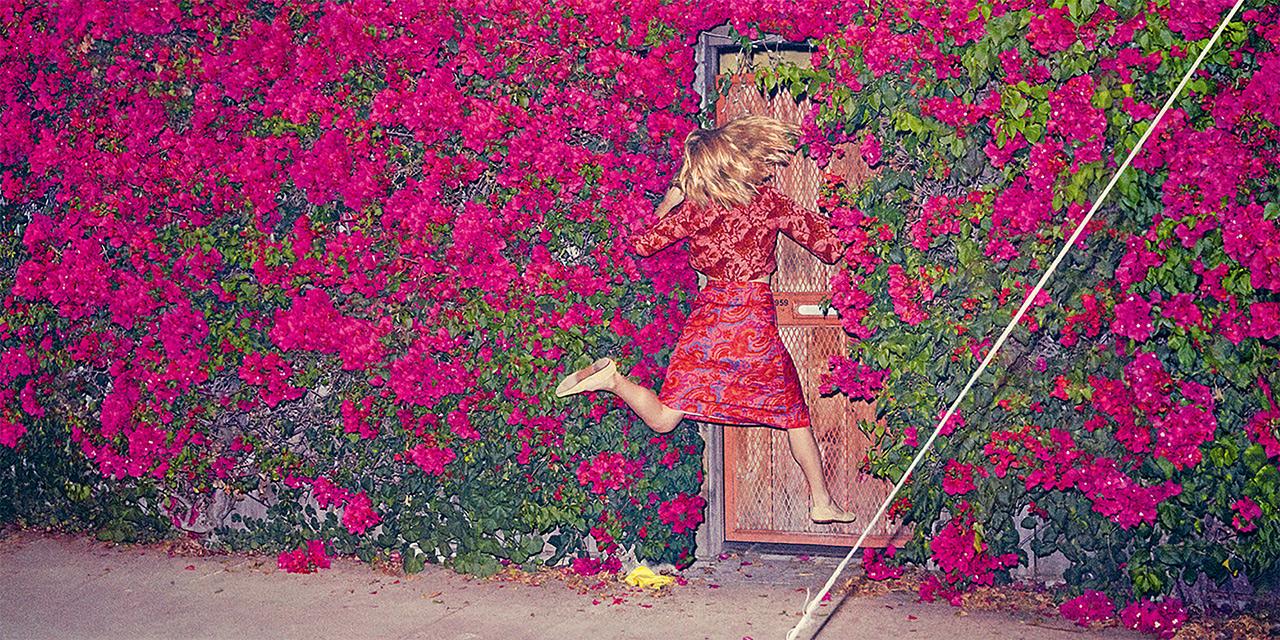 Plattencover: Mit Blumen bewachsene Wand mit Tür, Frau springt zur Tür