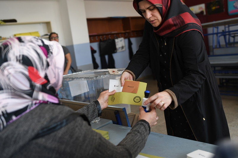 An electoral official hands a woman a stamp for her to mark her ballot