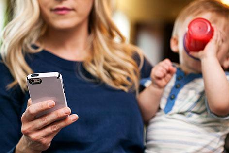 Mutter mit Baby auf dem Arm benutzt Smartphone